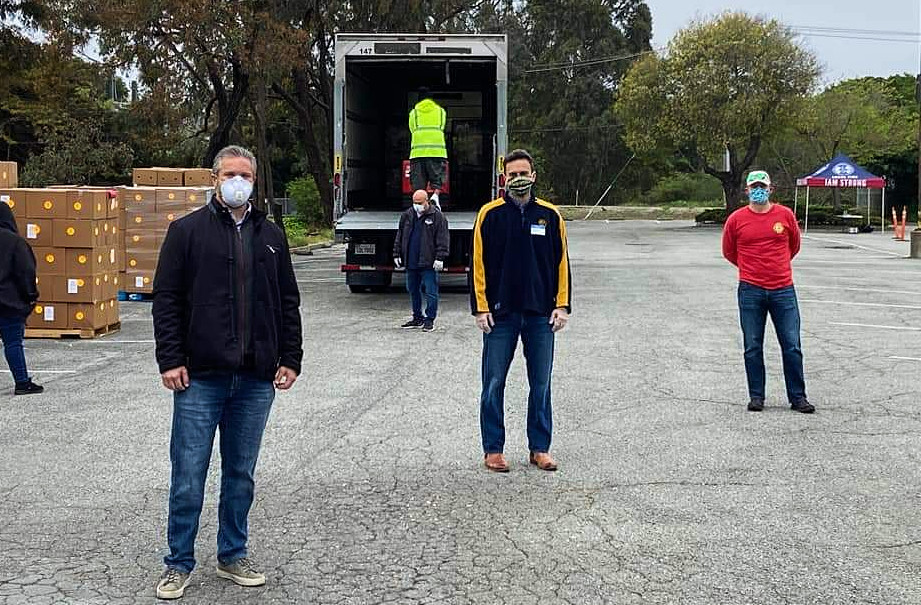 Local laborers' vehicles line up for food donations in Burlingame